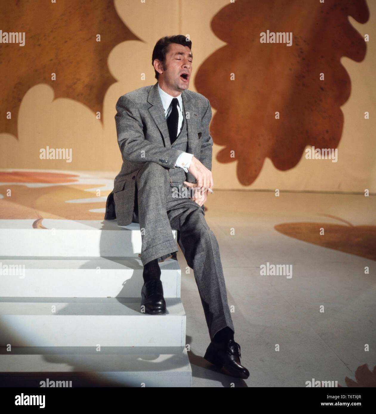 Der französische Modedesigner Schauspieler und Sänger, Jean-Claude Pascal singend auf einer Bühne, Deutschland Ende 1960er. El modisto francés, actor y cantante Jean-Claude Pascal cantando en un escenario, Alemania 1960. Foto de stock