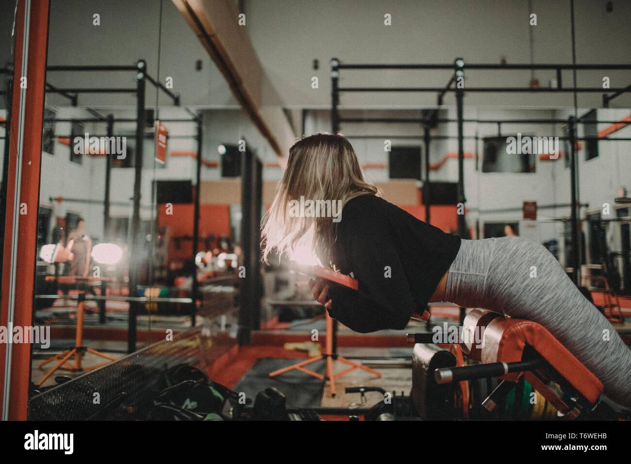 Mujer atractiva el levantamiento de pesos en Hyper Extension Bench en el gimnasio Foto de stock
