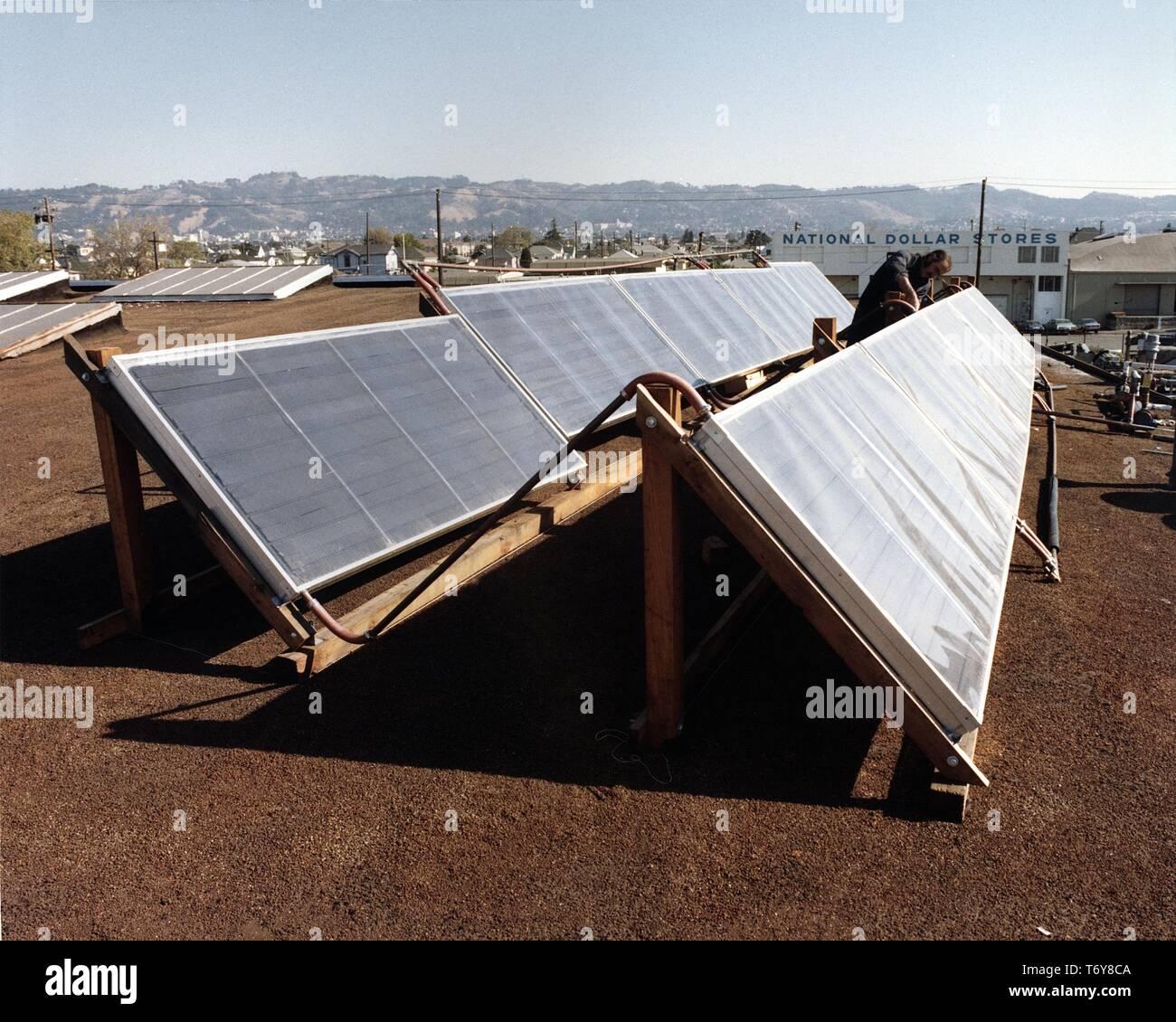 Un trabajador ajusta un panel solar montado sobre un techo durante un proyecto para hacer viable el lavado de botella reciclable en una escala mayor, de 1980. Imagen cortesía del Departamento de Energía de Estados Unidos. () Foto de stock