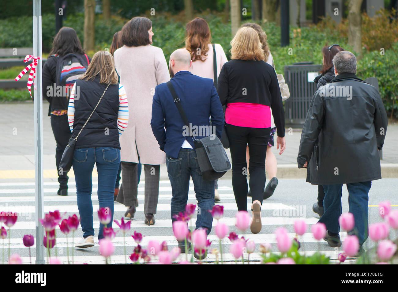 Un grupo de seguidores a caminar una milla en sus zapatos campaña por la igualdad de género de cruzar una calle. Imagen De Stock