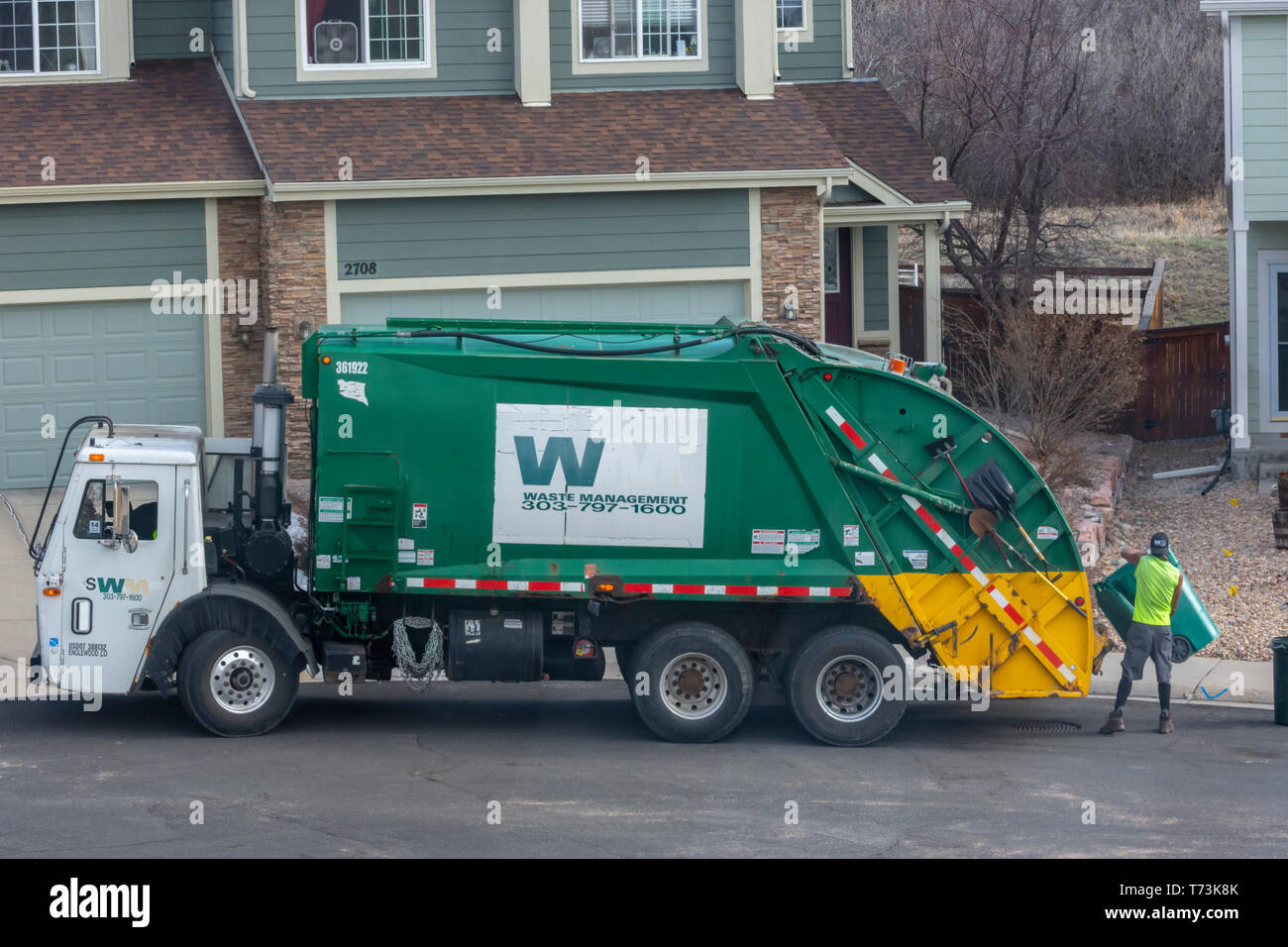 Un trabajador de la gestión de residuos se vacía de plástico verde, recipientes de basura en una zona residencial de Castle Rock, Colorado, EEUU. Foto tomada en abril. Imagen De Stock