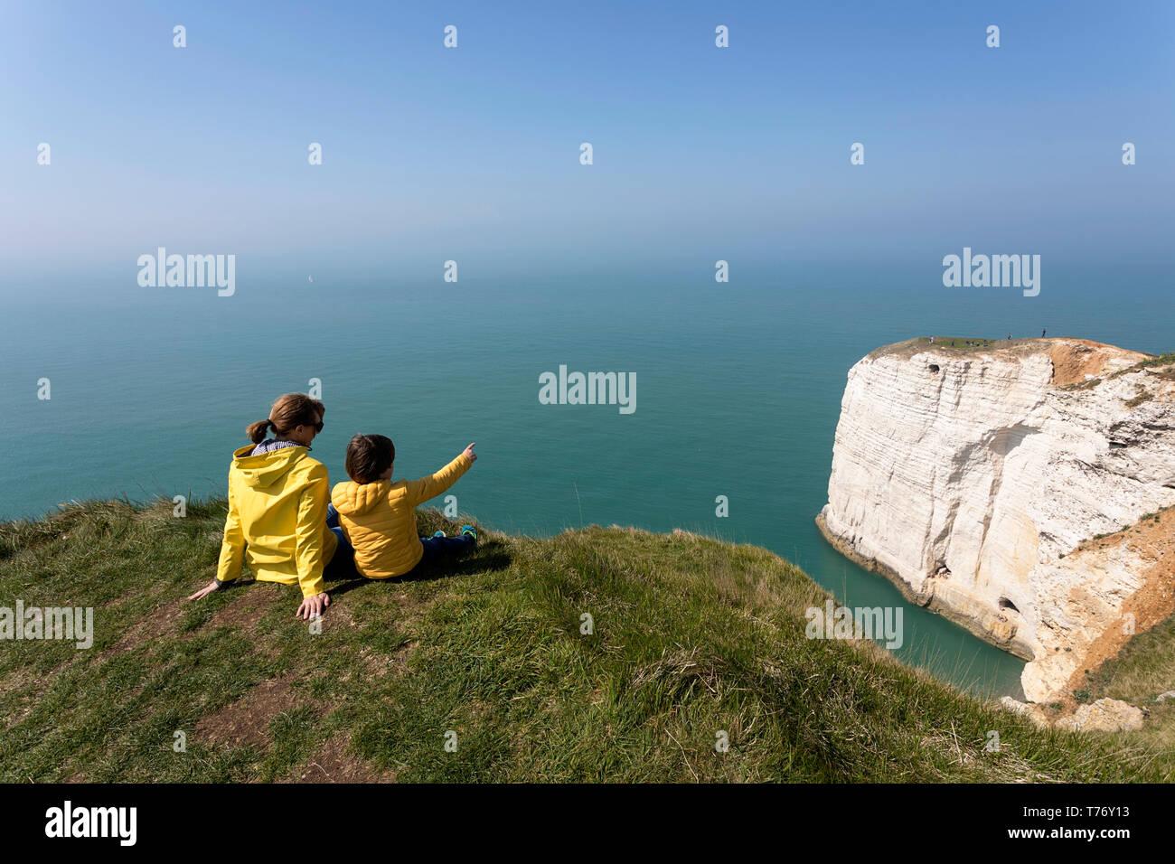 Francia, Normandía: Madre e hijo sentado sobre el césped cubierto de roca acantilados por encima del arco de Playa Etretat Foto de stock