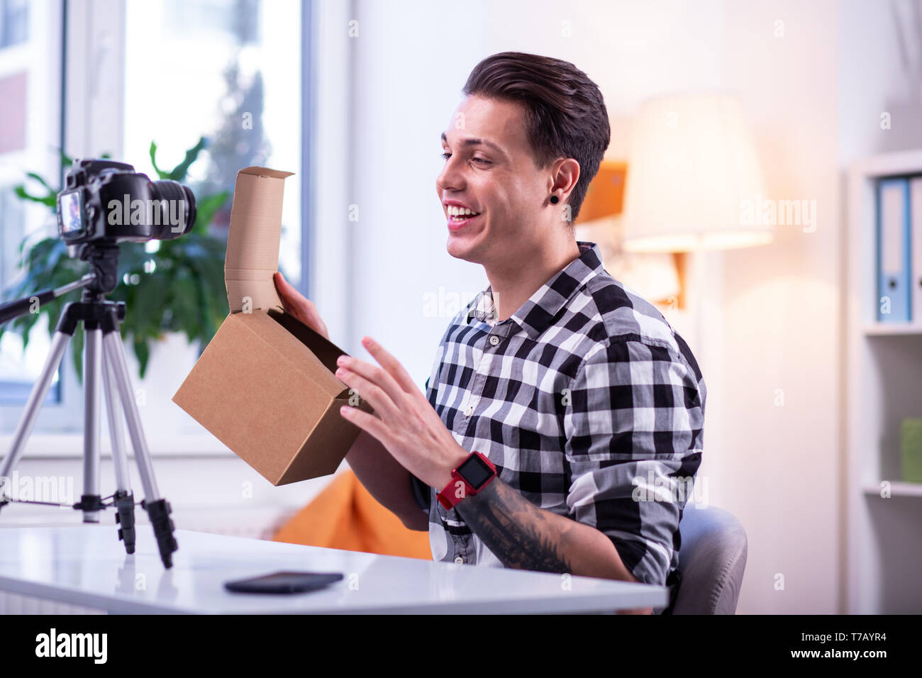 Alegre buen mozo con cejas afeitada con reloj electrónico rojo Foto de stock