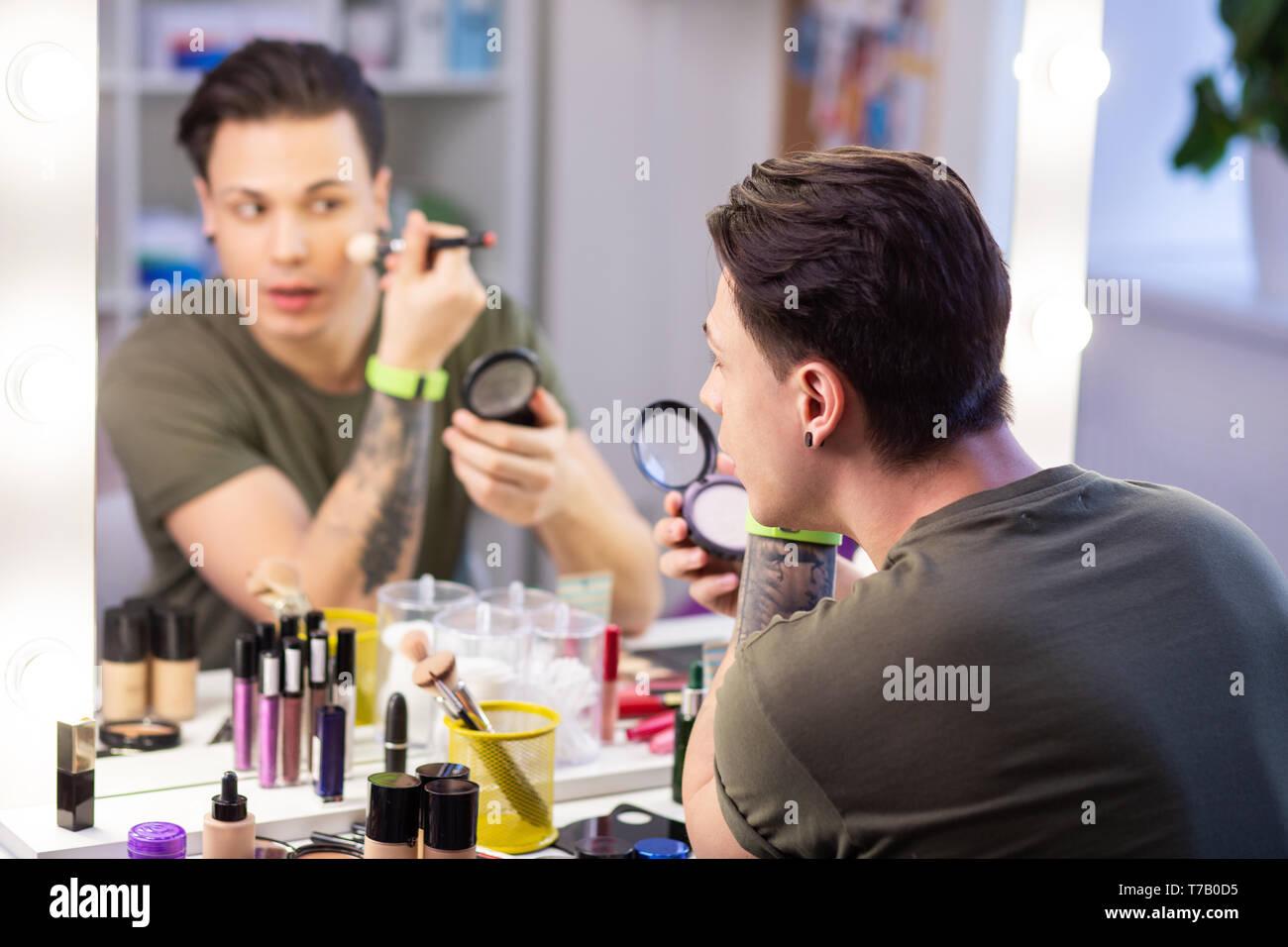 Curioso guapo arreglándose delante del espejo Foto de stock