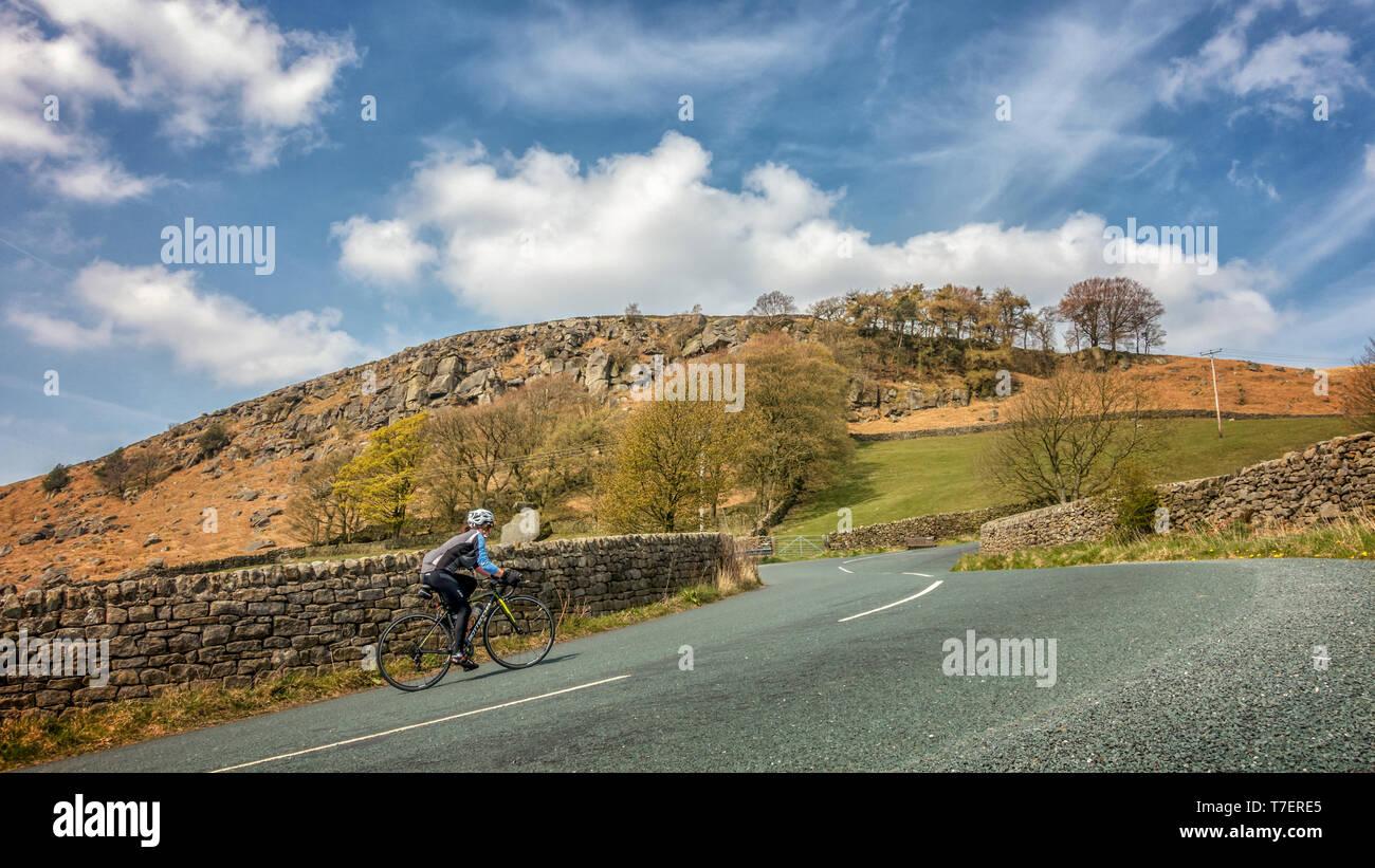 Ciclista femenino andar en bicicleta por la empinada subida de Côte de Barden Moor, parte del Tour de Yorkshire 2019 carrera ciclista ruta, Valles de Yorkshire, Reino Unido Foto de stock
