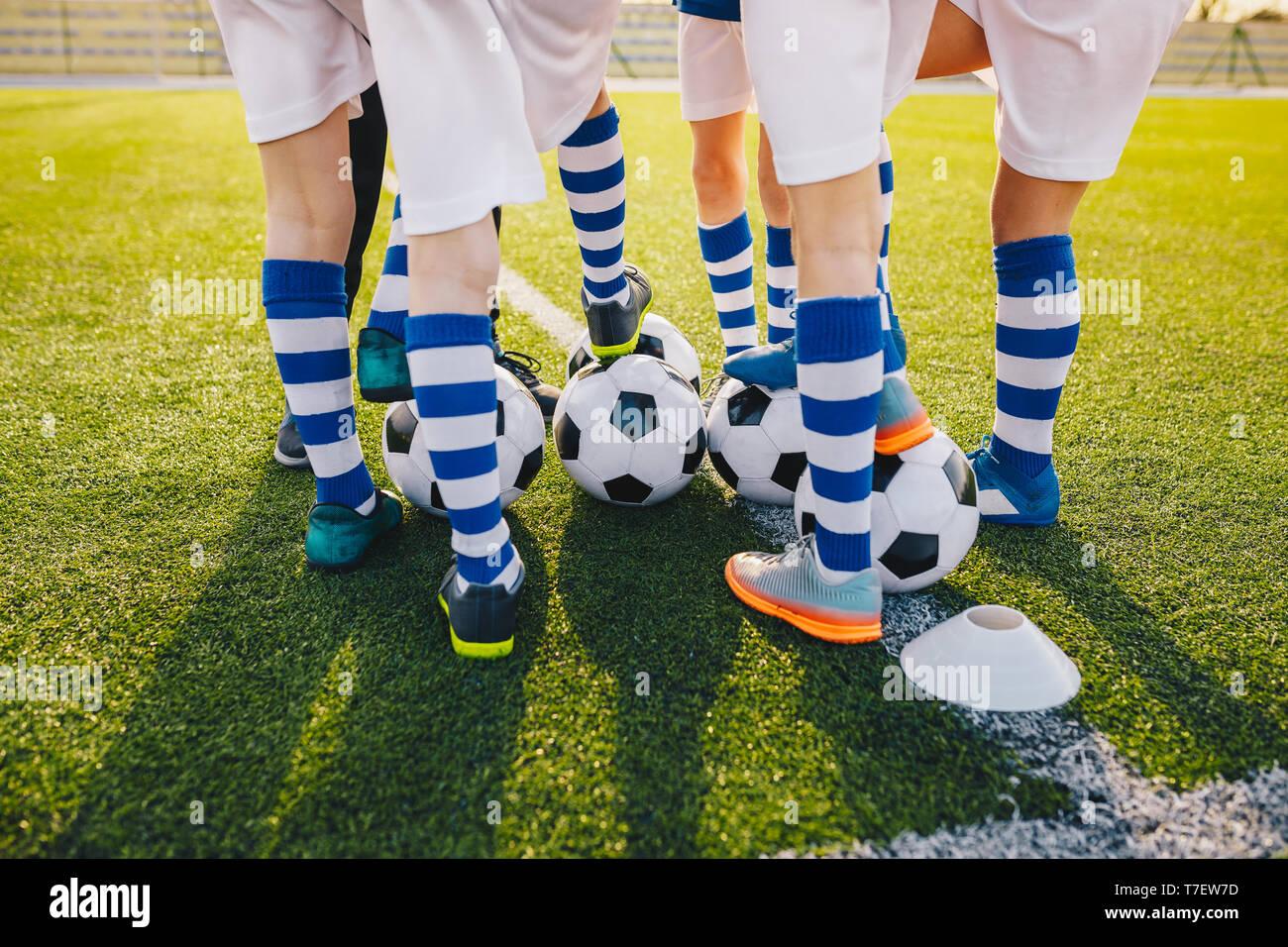 Grupo de jóvenes jugadores de fútbol en entrenamiento de fútbol. Las piernas de niños pateando balones de fútbol en el campo. Atardecer de verano en el fondo. Entrenamiento de fútbol bac Foto de stock