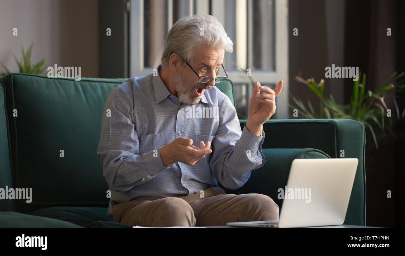 Los cabellos grises emocionado hombre sorprendido por la increíble noticia en portátil Foto de stock