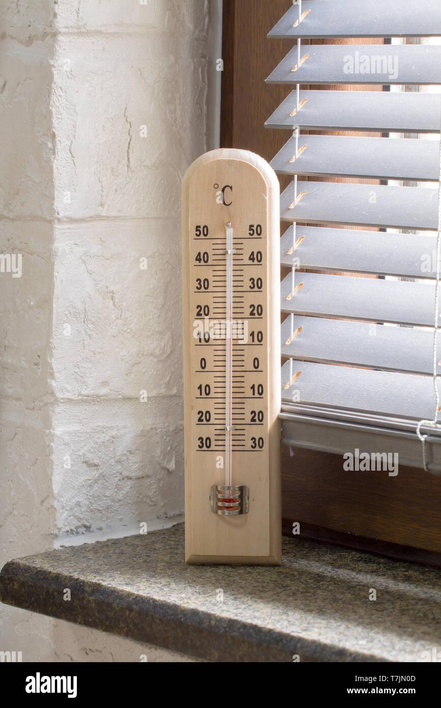 Un termómetro de madera con escala analógica midiendo la temperatura colocado cerca de la ventana Foto de stock