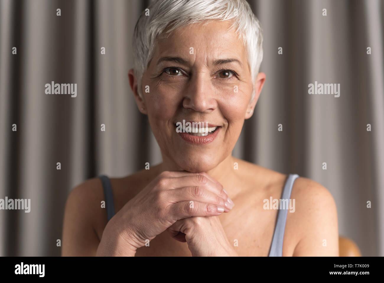 Hermosa naturales altos mujer con cabello gris corto mirando a la cámara, el concepto de belleza natural Imagen De Stock