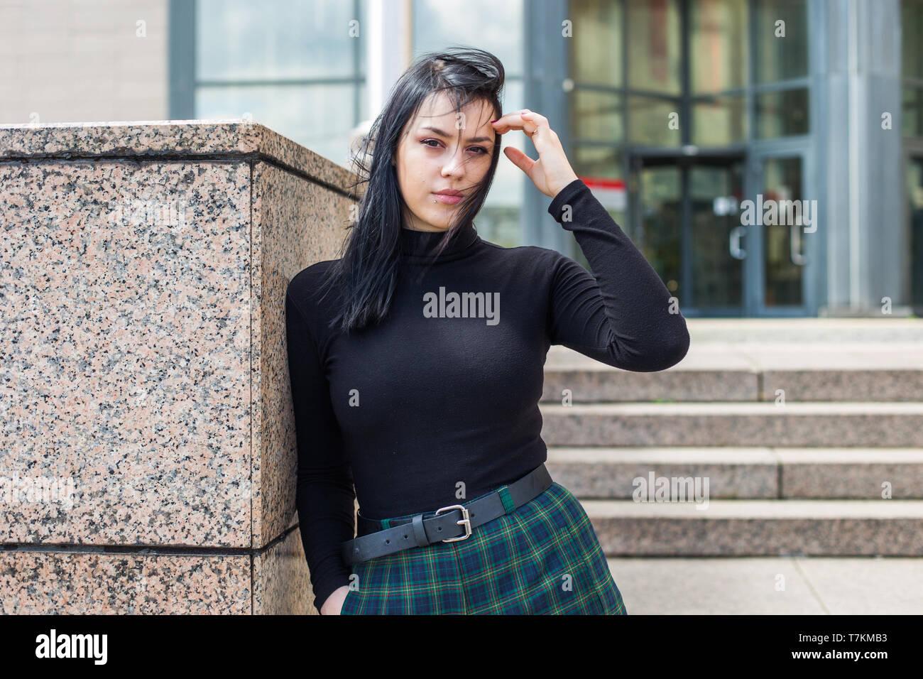 Joven en camisa negra y pelo negro de pie en frente del edificio de oficinas, de medio cuerpo, confianza Imagen De Stock