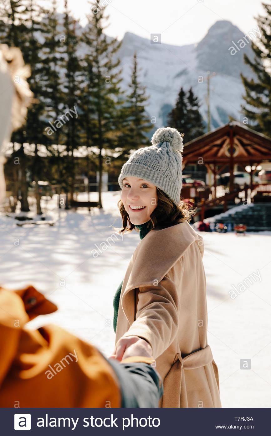 Mujer sonriente sosteniendo la mano del novio en la nieve Imagen De Stock