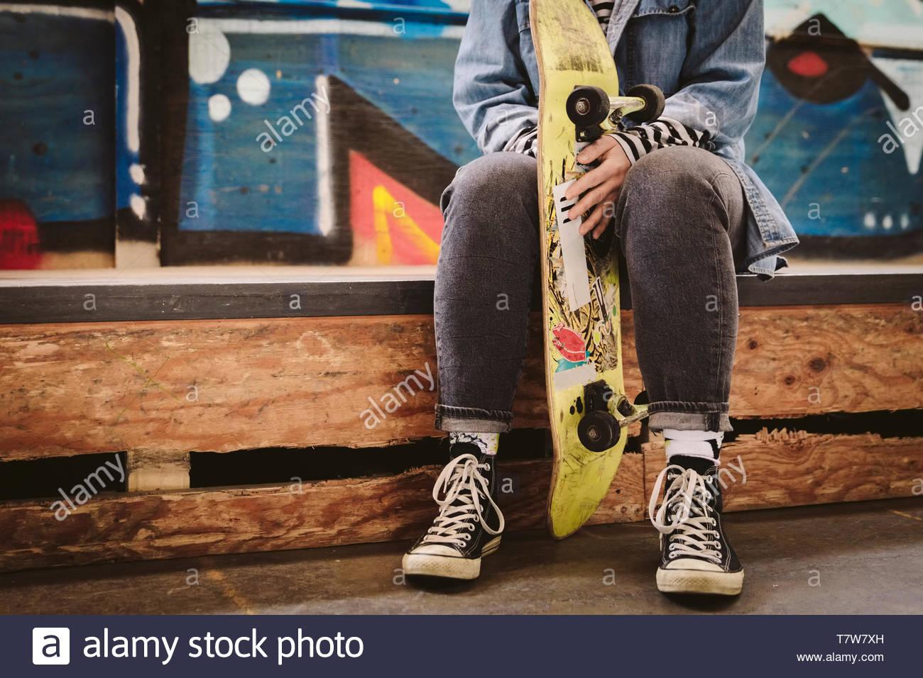 Mujer sosteniendo en monopatín skate park interior Imagen De Stock