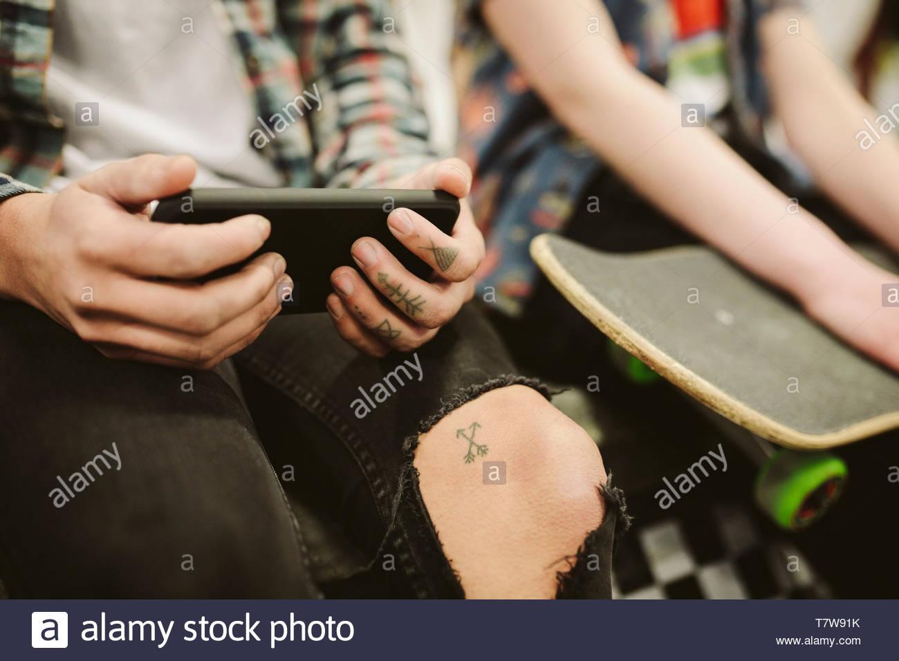 Cierre skateboarders adolescentes con tatuajes con teléfonos inteligentes. Imagen De Stock