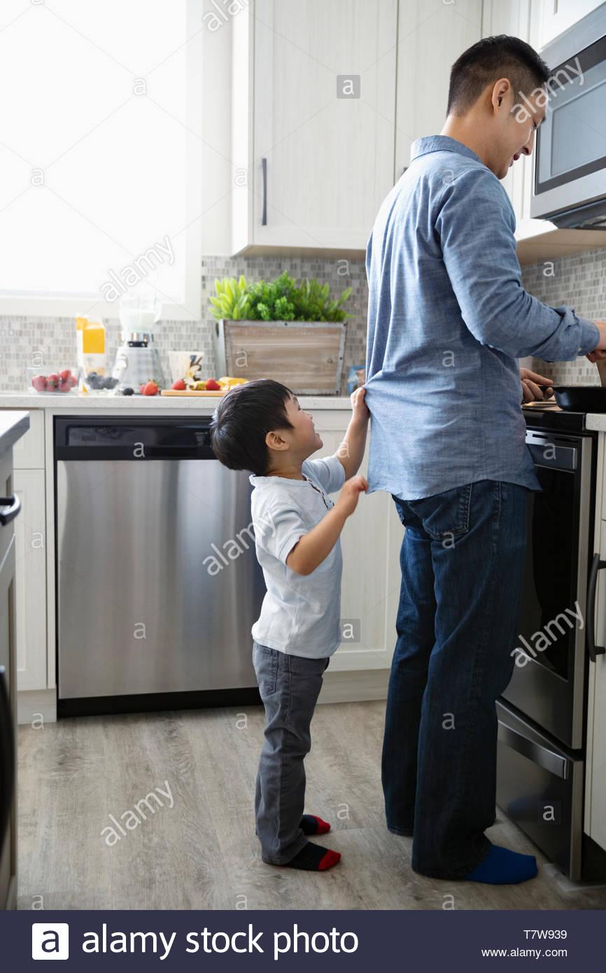 Lindo hijo de tirón al padre cocinar en la cocina Imagen De Stock