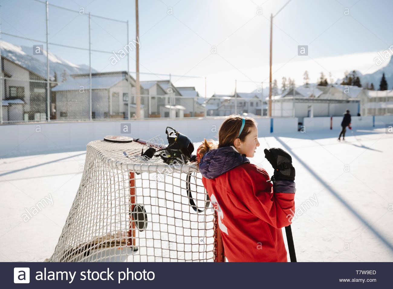 Niña jugando hockey sobre hielo al aire libre, descansando en el objetivo Imagen De Stock