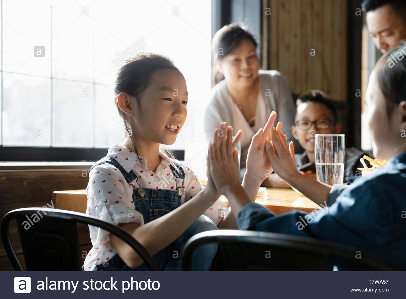 Hermanas tocando palmas juego en restaurante Imagen De Stock
