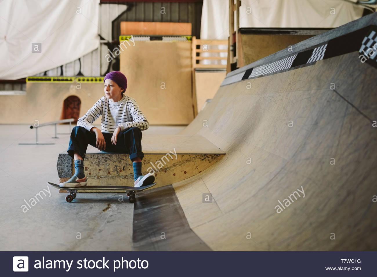 Adolescente con skateboard sentado en la rampa de skate park interior Imagen De Stock