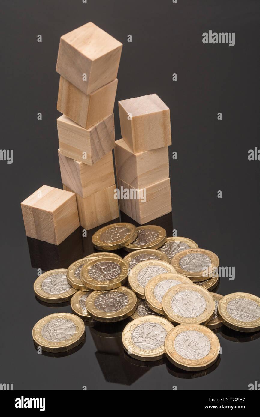 Nueva libra monedas + desordenados / cayó ladrillos y bloques de madera. Depreciación de la libra esterlina, la caída en el valor de la libra £, bloqueos, libra vender la reducción de las tasas de interés Foto de stock
