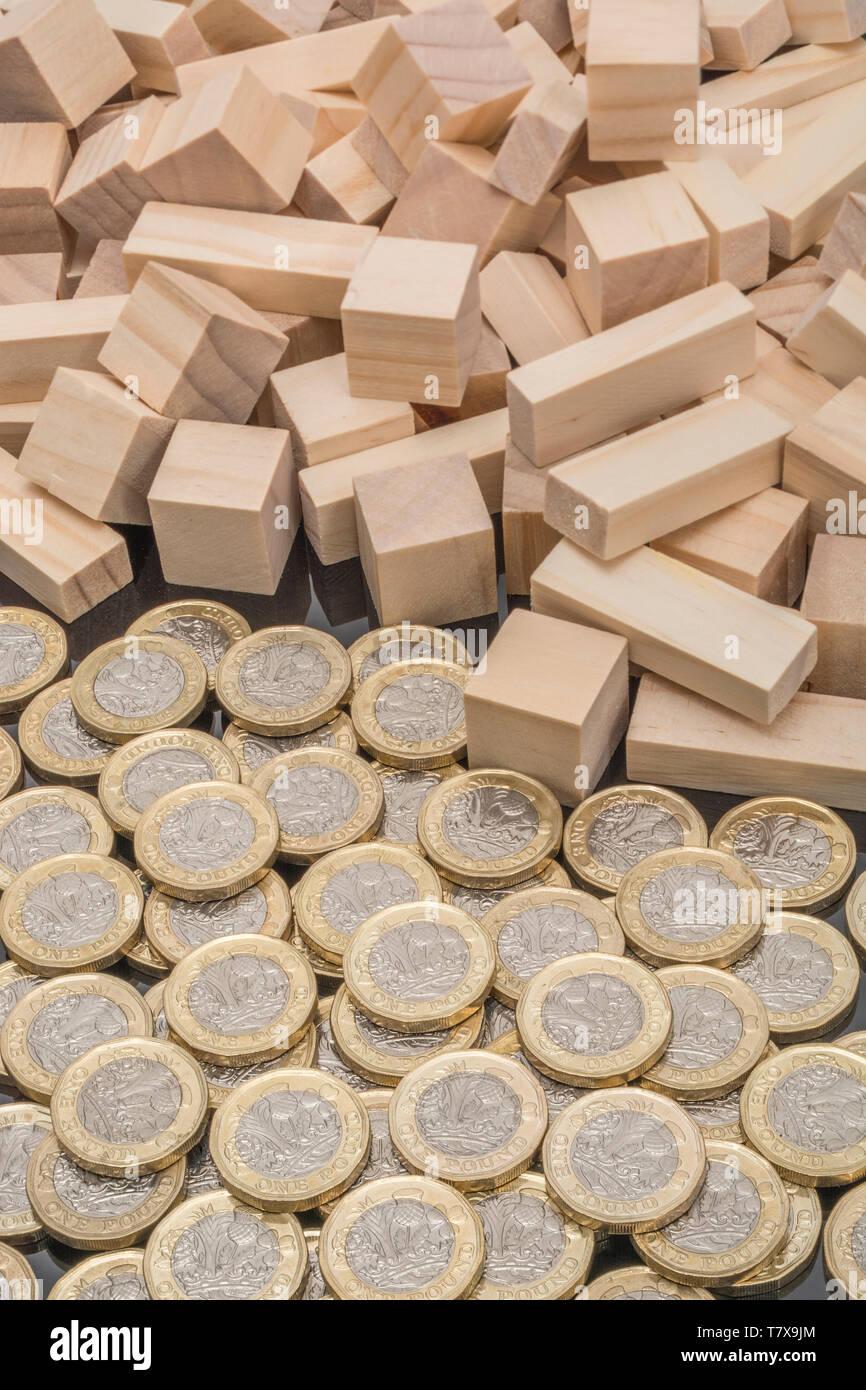 Nuevas monedas de libra + ladrillos y bloques de madera revolteados/tambaleados. Libra esterlina desplome, caída en £, libra que vende-fuera el desplome de la tasa de interés, desplome del mercado 2020 Foto de stock