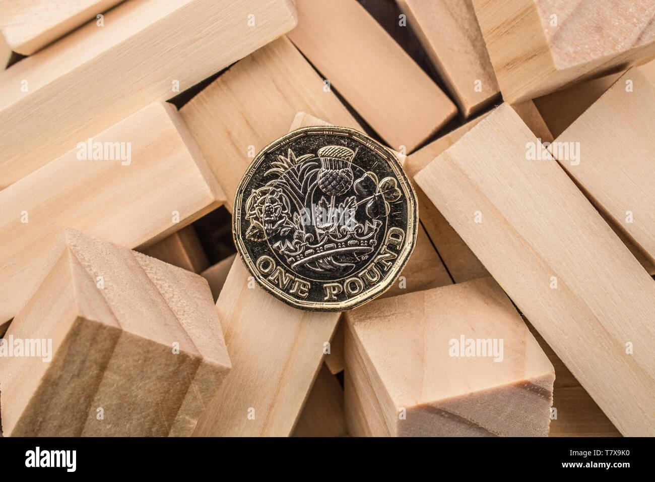 Nuevas monedas de libra + ladrillos y bloques de madera revolteados/tambaleados. Libra esterlina desplome, caída en £, libra venta-off el tipo de interés desplome, caída del mercado 2020 Foto de stock