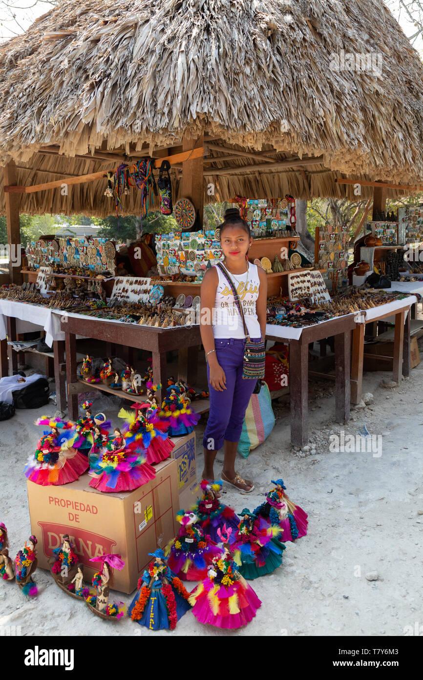 Puesto en el mercado de América Latina y mujer indígena joven comerciante vender artículos artesanales; Tikal, Guatemala Centroamérica Foto de stock