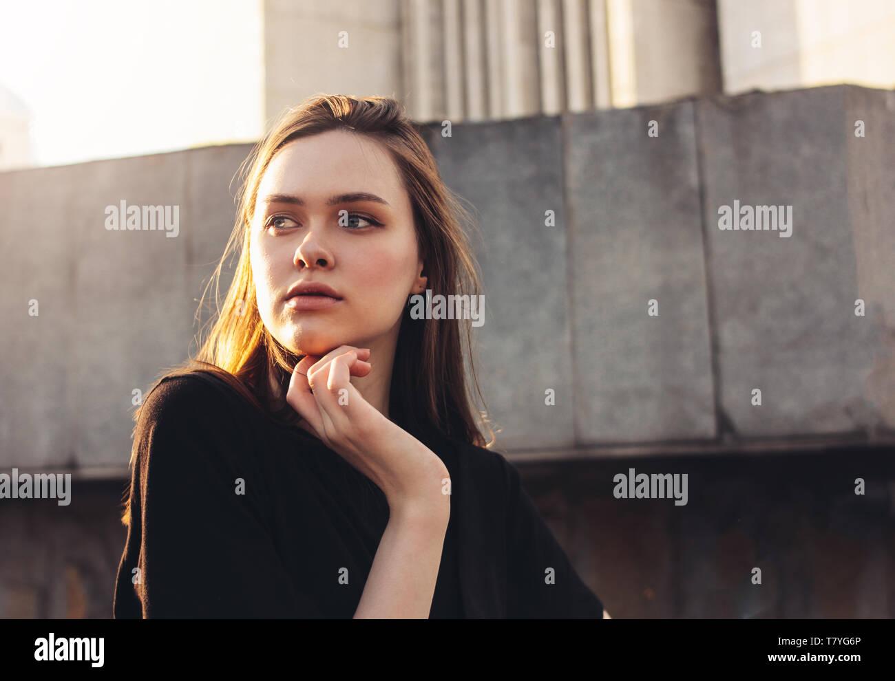 Close Up retrato de un hermoso pelo largo, niña modelo de moda en el atardecer en las calles de la ciudad Foto de stock
