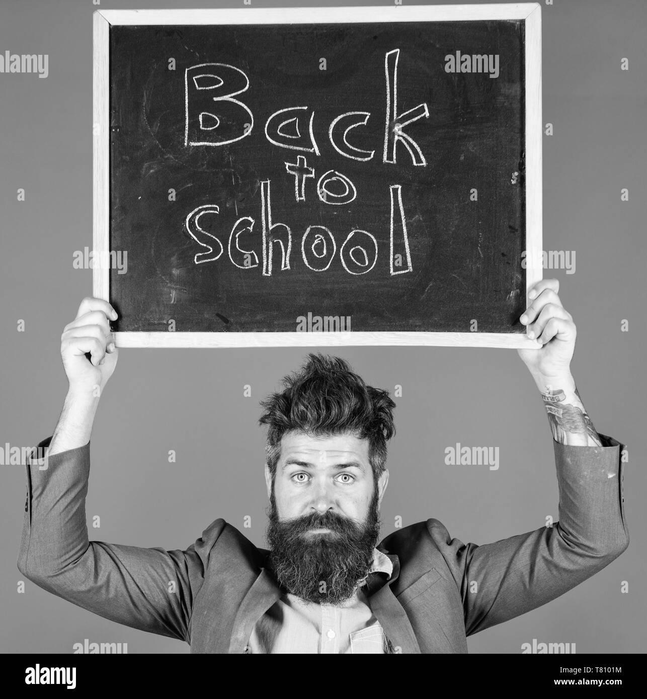Maestro hombre barbado tiene pizarra con inscripción back to school fondo azul. Profesor con deslucido cabello estresante sobre el año escolar comienza. Enseñanza ocupación estresante. No se turbe vuestro corazón. Imagen De Stock