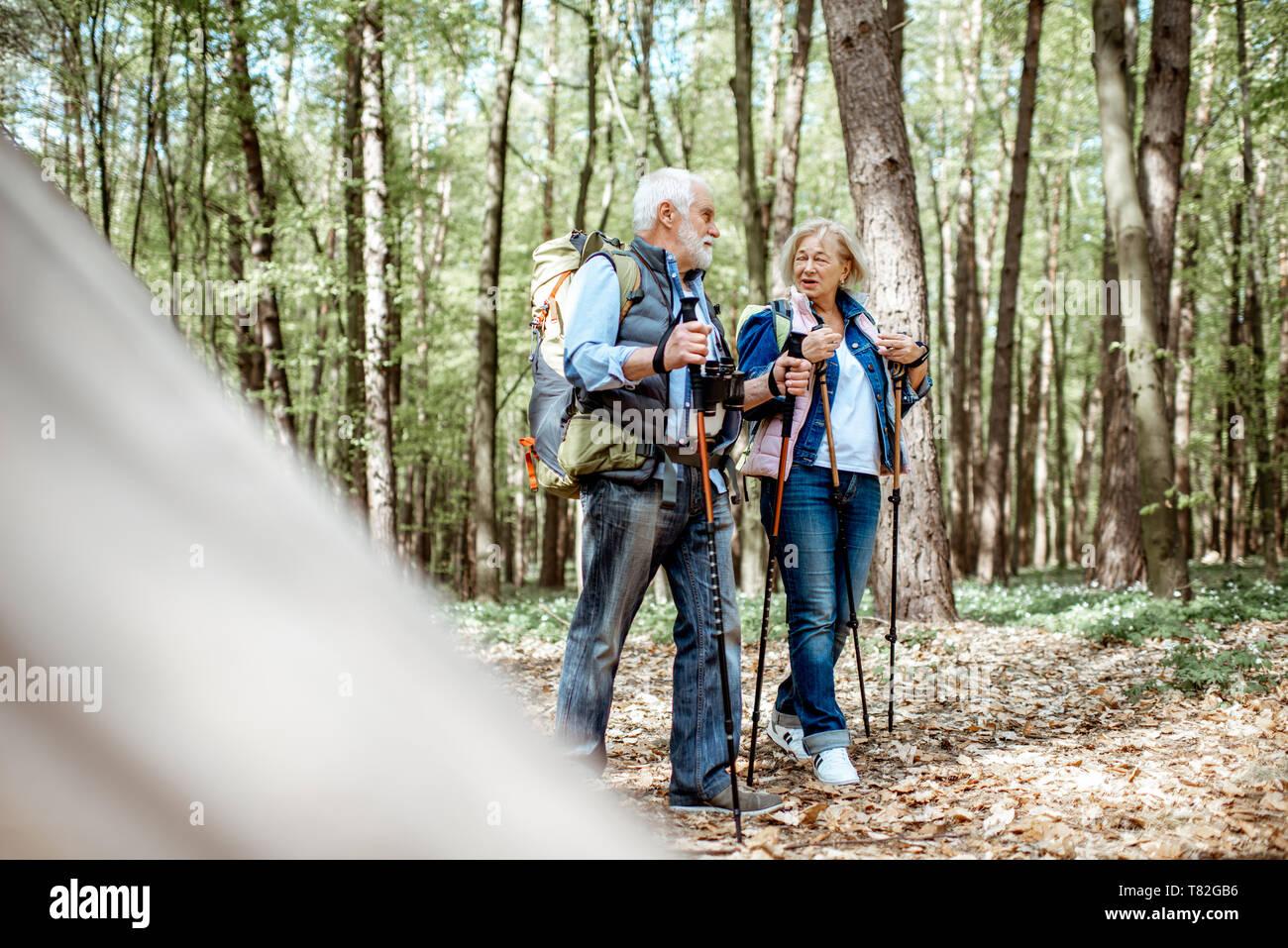 Hermosa pareja senior caminatas con mochilas y bastones de trekking en la selva. Concepto de la vida activa a la jubilación Foto de stock