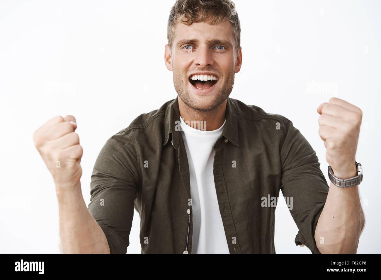 Yo creo en ti. Retrato de vítores de apoyo guapo con ojos azules y amplia sonrisa blanca intentando alentar amigo aprietan puños en victoria Imagen De Stock