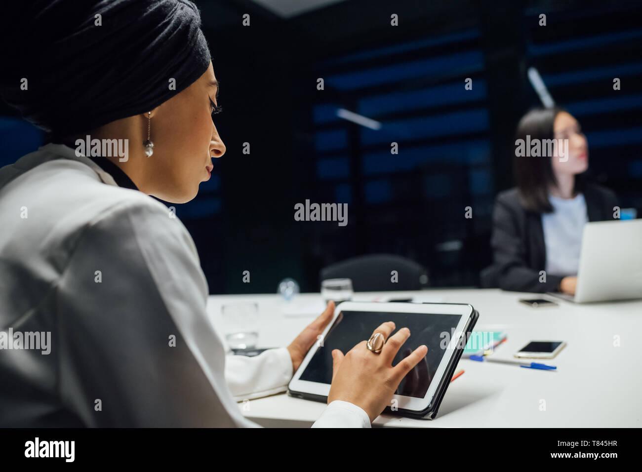 La empresaria utilizando tablet digital durante la presentación de Office, vista sobre el hombro Foto de stock