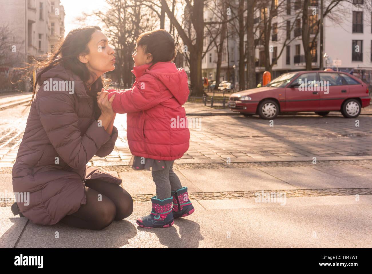Besos Madre Hija sobre pavimento Foto de stock