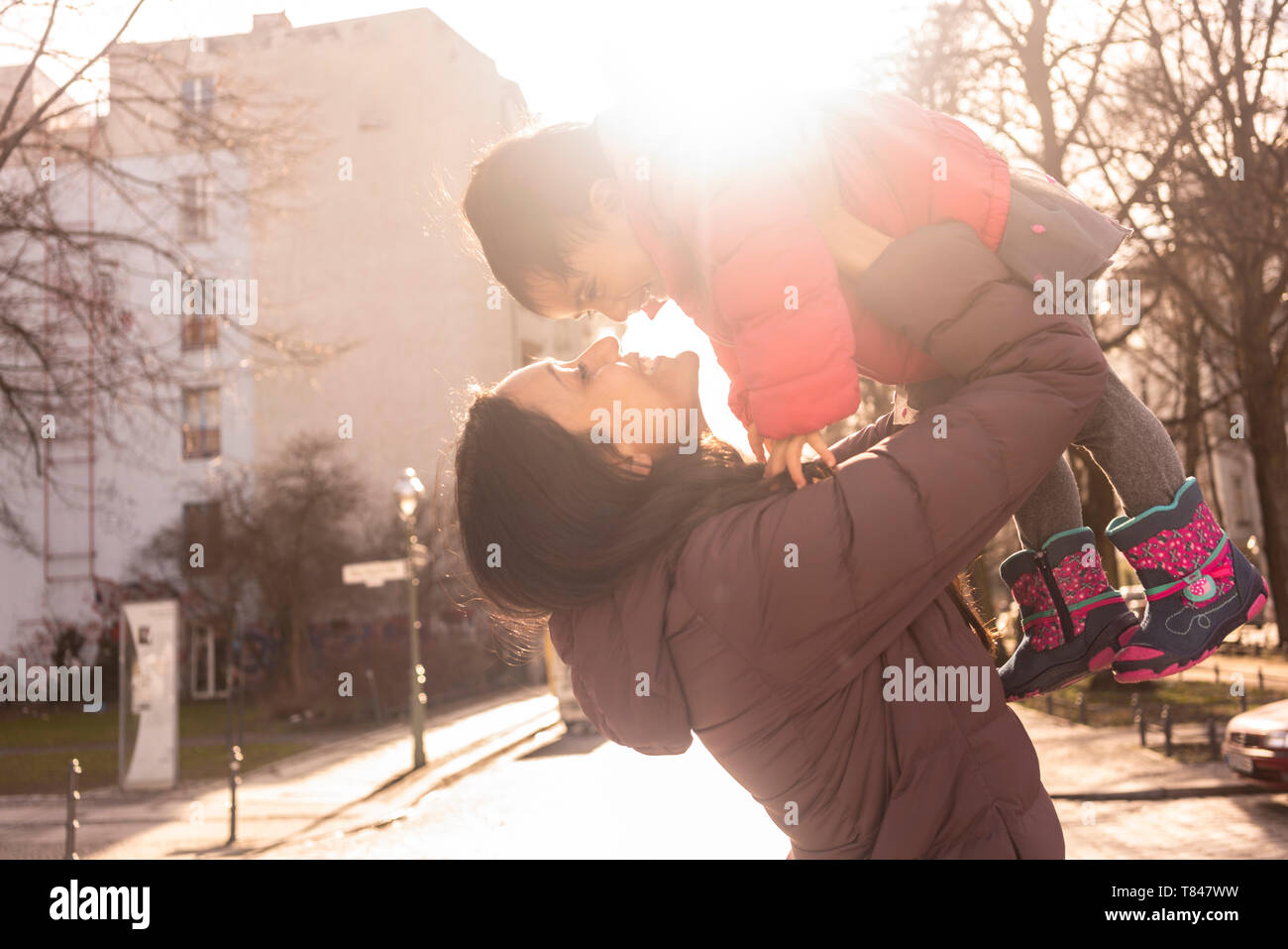 Madre Hija de elevación en el aire sobre pavimento Foto de stock