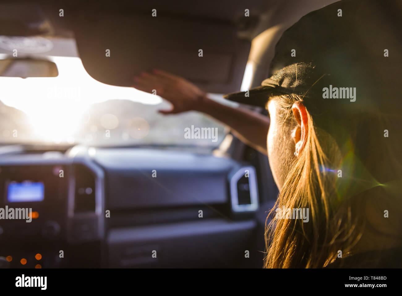 Mujer pasajero en el asiento delantero del coche el blindaje de los ojos de la luz solar, vista sobre el hombro Foto de stock