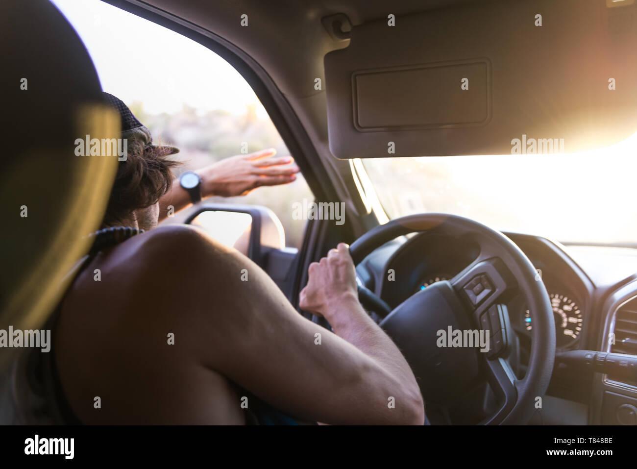 El hombre coche el blindaje de los ojos de la luz solar, vista sobre el hombro Foto de stock