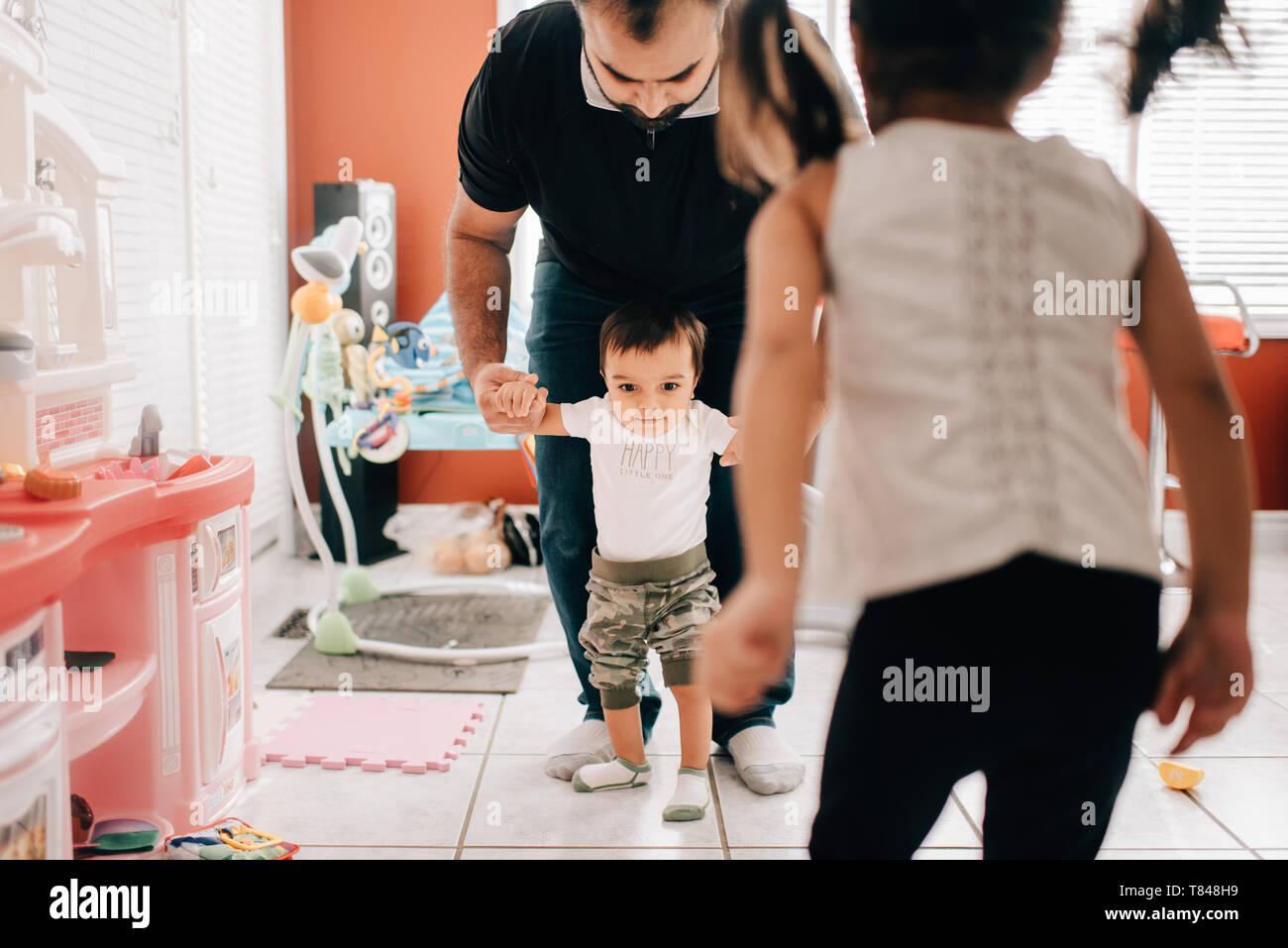Niña delante del padre caminar hermanito en la cocina Foto de stock