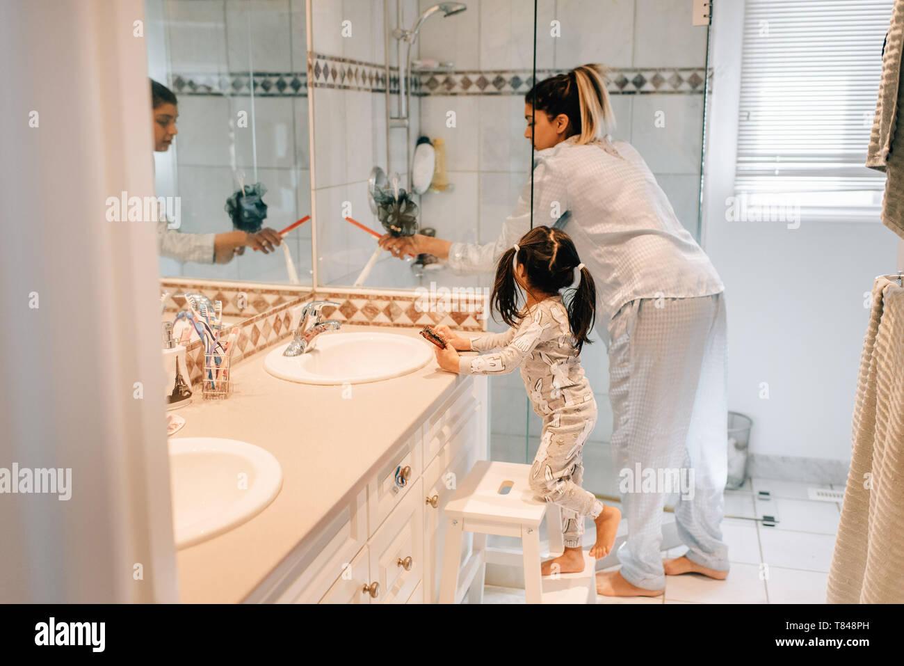 Niña y madre preparándose en el baño. Foto de stock