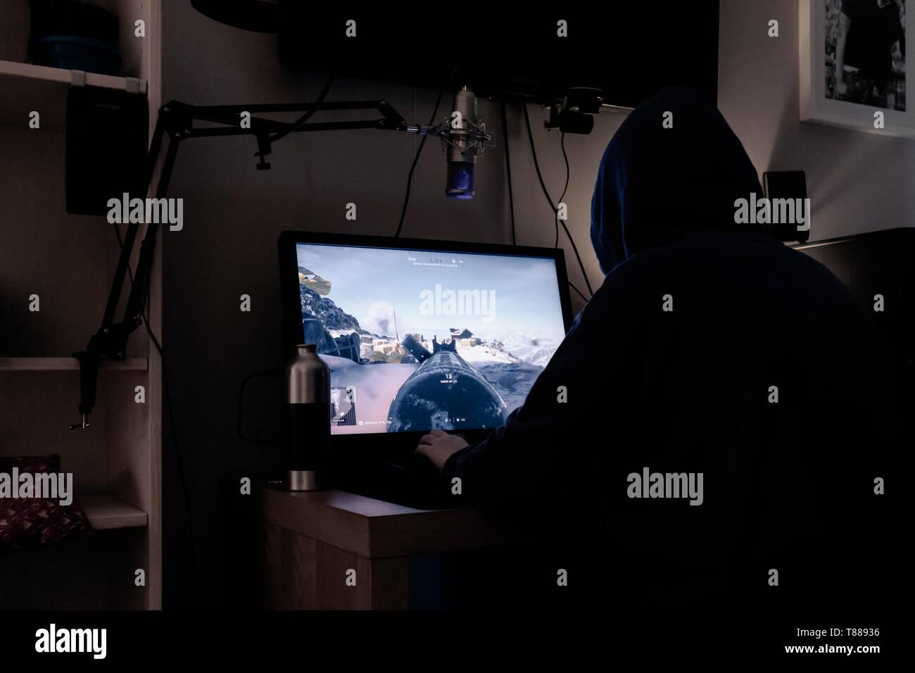 Adolescente sentado en la oscuridad en el ordenador de sobremesa para juegos Foto de stock