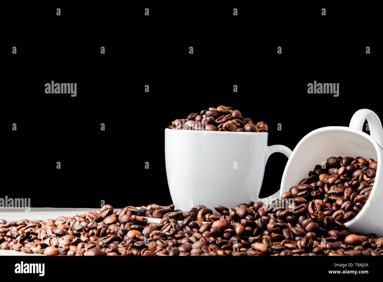 Café Negro en taza blanca y granos de café sobre fondo negro. Vista superior, espacio para el texto Foto de stock