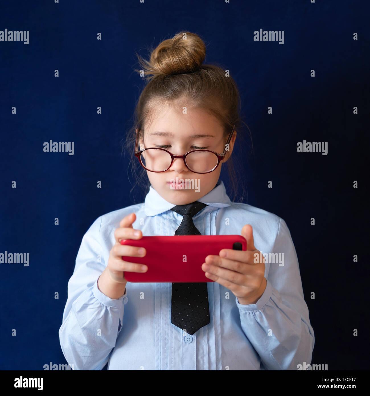 Estudiante de grado elemental la celebración de smartphone. Expressionless escolares en uniforme y espectáculos charlando. Little Schoolgirl con teléfono móvil sobre fondo azul oscuro. Pasatiempo moderno, estudiando romper Imagen De Stock