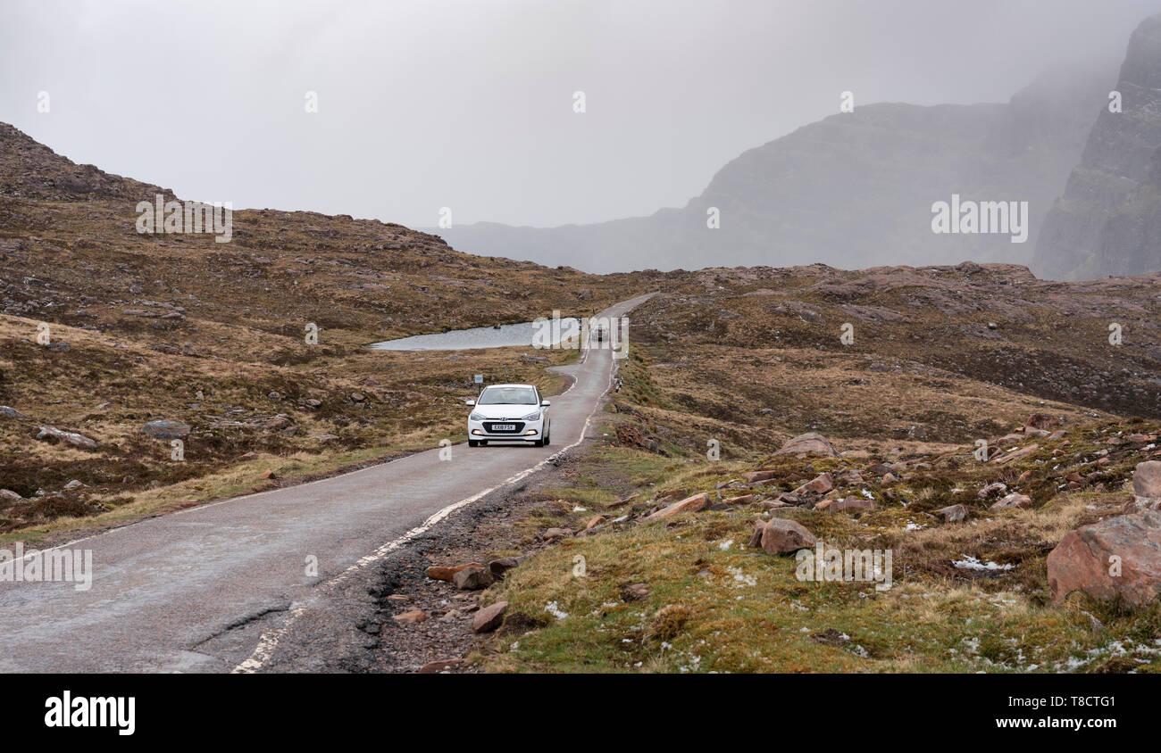 Vista de una sola vía en carretera Bealach na Ba pasar sobre la costa norte de la península de Applecross 500 ruta de conducción en el norte de Escocia, Reino Unido Foto de stock