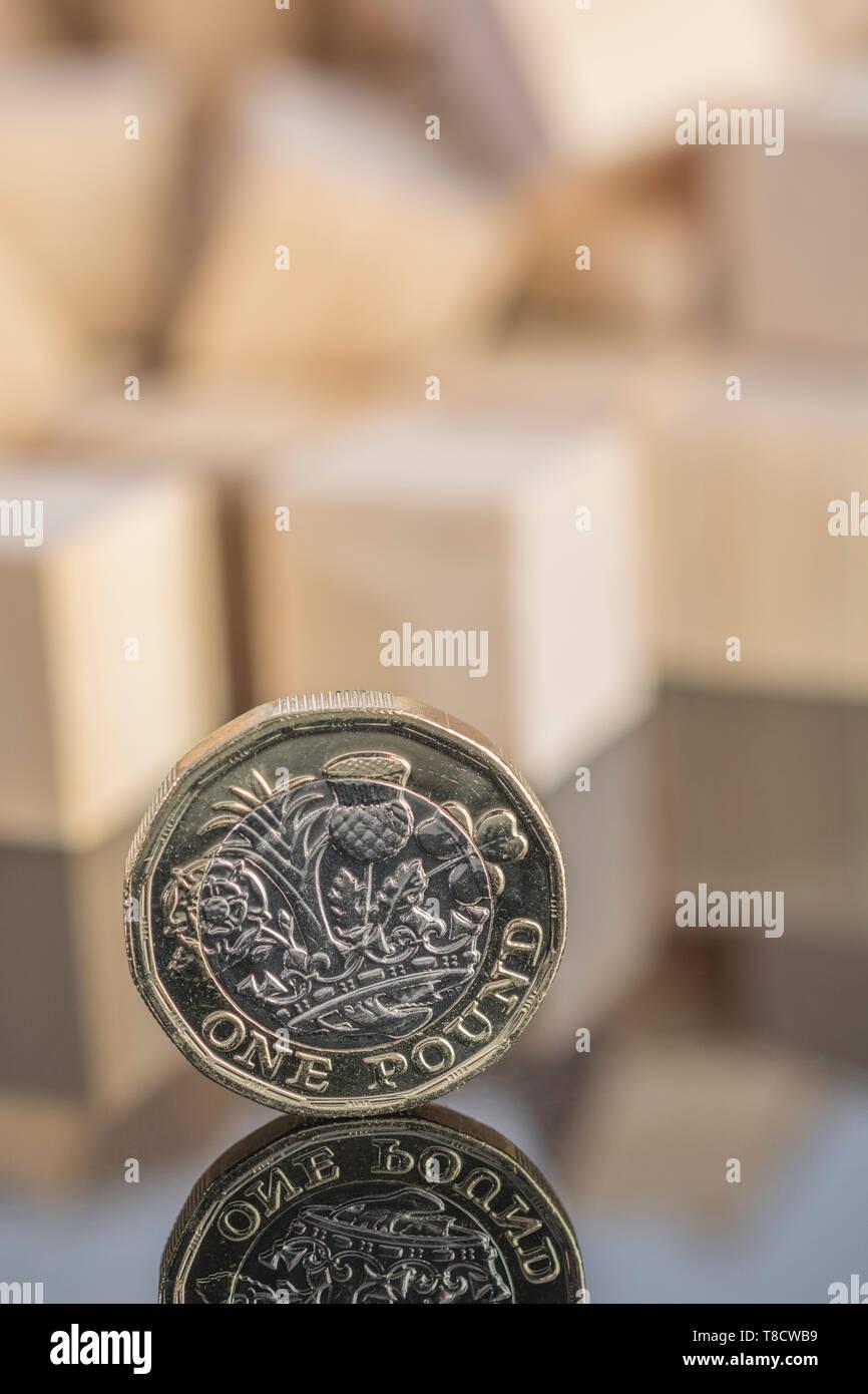 Reino Unido Nueva libra moneda sobre fondo reflectante con ladrillo de madera dispersos. Para el colapso de la libra, colapso de la libra esterlina, caída en el valor de la libra esterlina, desplome del mercado 2020. Foto de stock