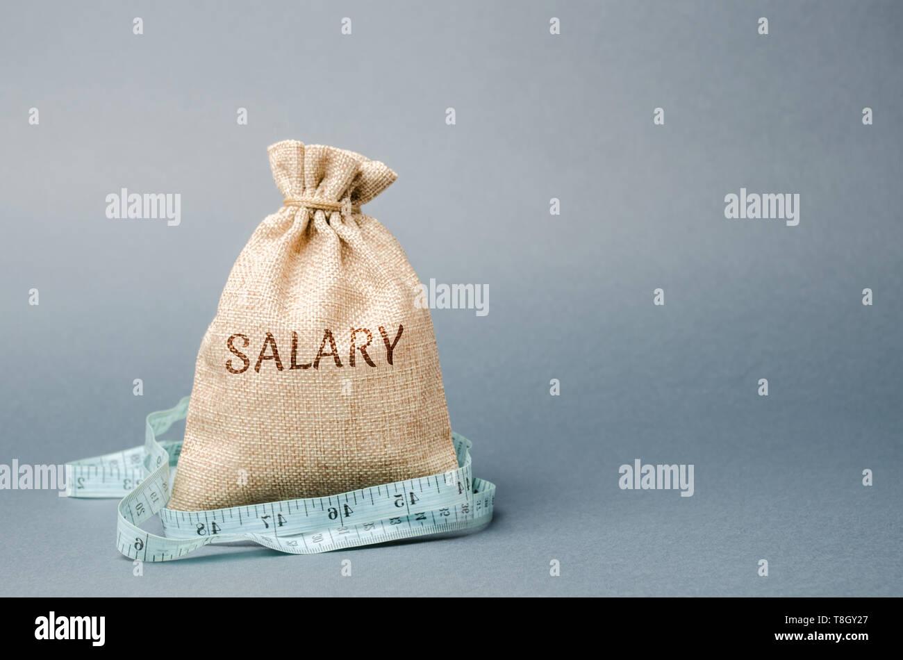 Bolsa de dinero con la palabra salario y cinta métrica. Los recortes salariales. El concepto de beneficio limitado. La falta de dinero y de la pobreza. Los pequeños ingresos. La reducción de los salarios. Foto de stock