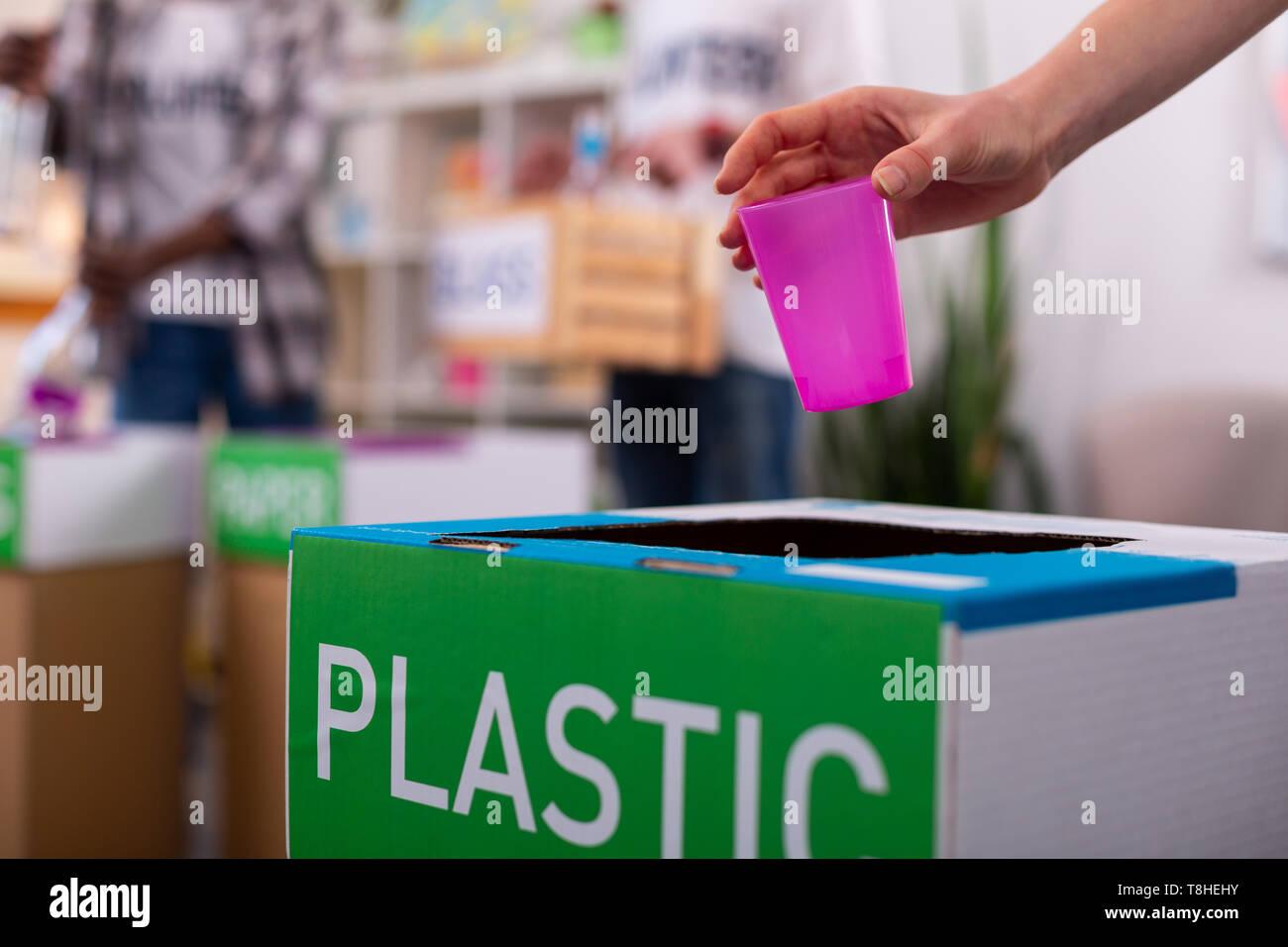 Chica colocando cristal rosado en el cuadro de clasificación de los residuos de plástico Foto de stock