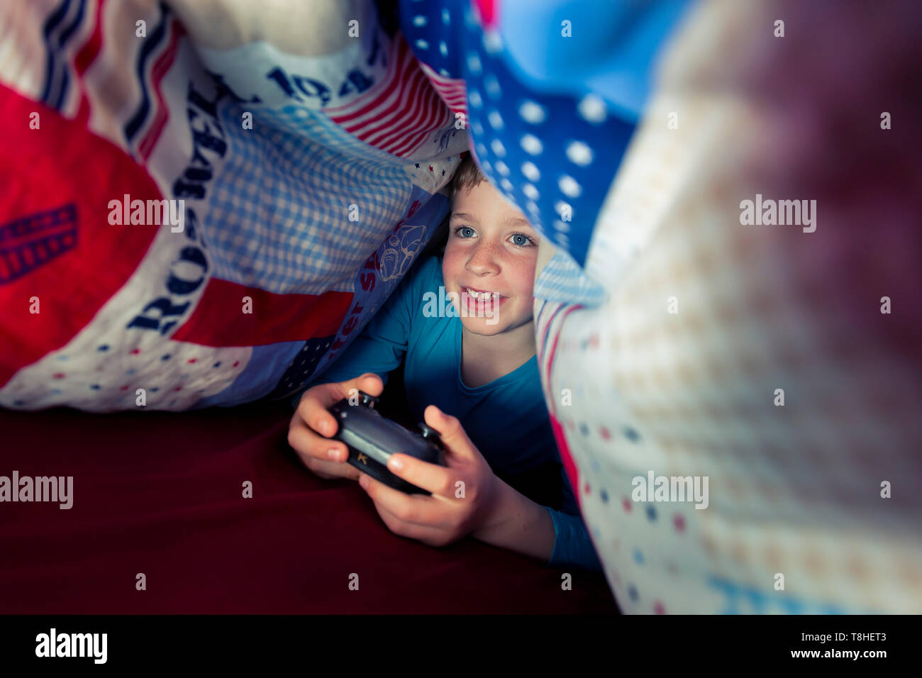 El muchacho, de 8 años, sectretly jugando un juego de ordenador en la cama Foto de stock