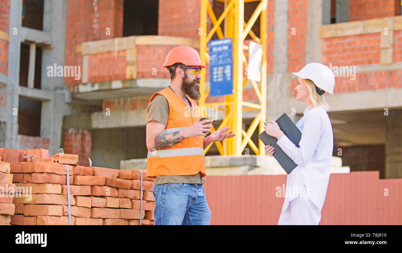 Construcción de relaciones entre los clientes y los participantes de la industria de la construcción. El concepto de comunicación del equipo de construcción. Mujer ingeniero y brutal builder comunicarse sitio en construcción de fondo. Imagen De Stock