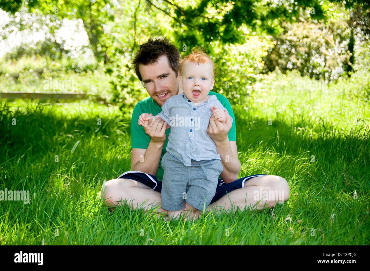 Los jóvenes papá con Baby Boy, sentados al aire libre en el jardín en un día soleado. Imagen De Stock