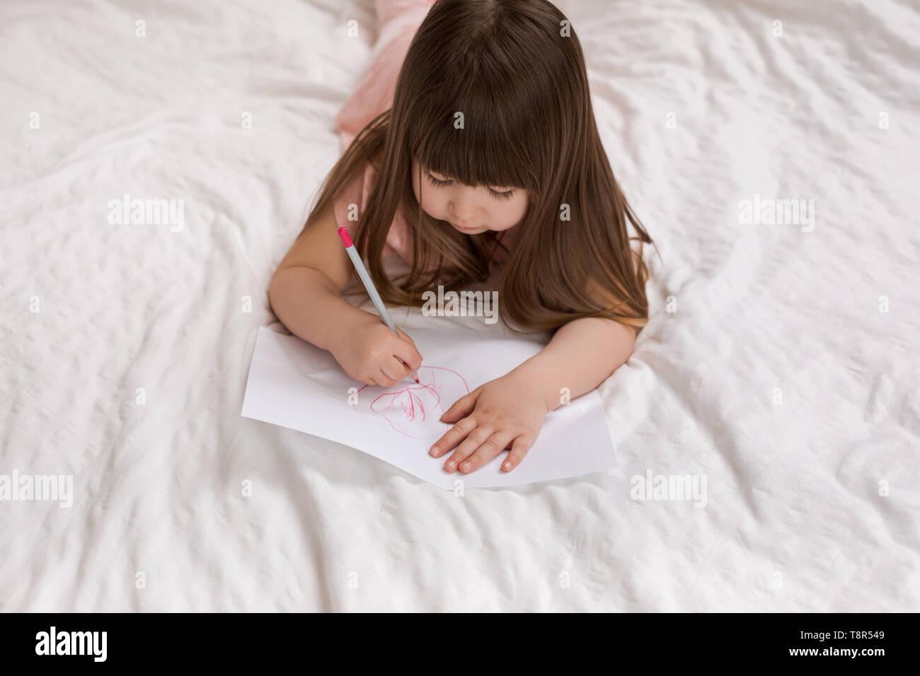 Cute Little Girl dibujar imágenes mientras estás acostado en la cama. Kid Pintura en casa vista superior. Foto de stock