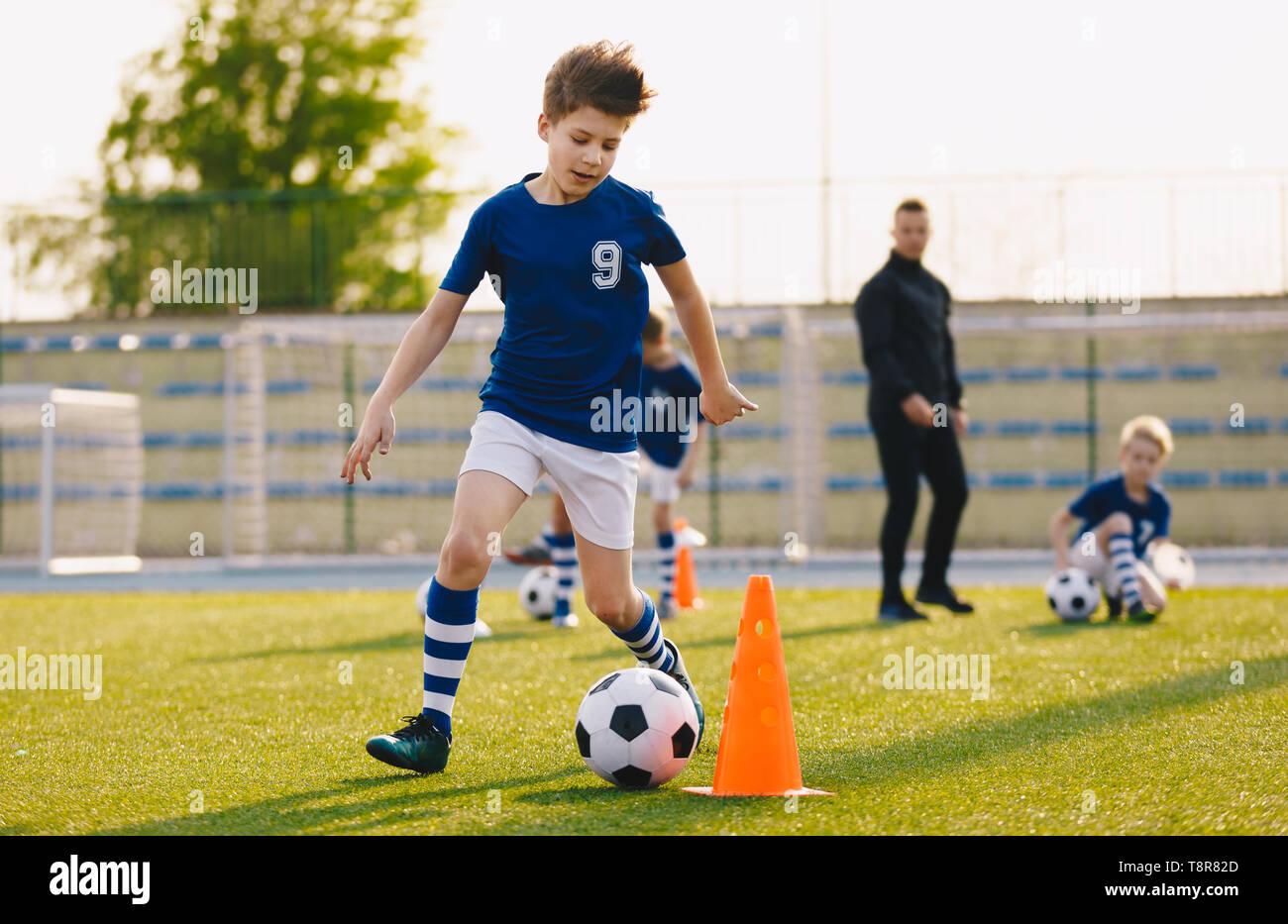Los niños formación regateando en un campo de fútbol. Niños corriendo la bola. Los jugadores de fútbol de desarrollar sus habilidades técnicas. Los niños entrenamiento con pelotas y conos. S Foto de stock