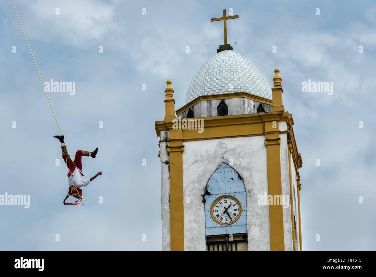 Volador lleva a cabo delante de la Iglesia de la Asunción en Papantla, Veracruz, México. La Danza de los voladores es un indígena totonaco ceremonia en la que participaron cinco participantes que suban un palo de treinta metros. Cuatro de estas cuerdas de amarre alrededor de su cintura y el viento el otro extremo alrededor de la parte superior del poste para descender a la tierra. El quinto participante permanece en la parte superior del poste, tocando la flauta y un pequeño tambor. La ceremonia ha sido inscrito como Obra Maestra del Patrimonio Oral e Inmaterial de la Humanidad por la UNESCO. Imagen De Stock
