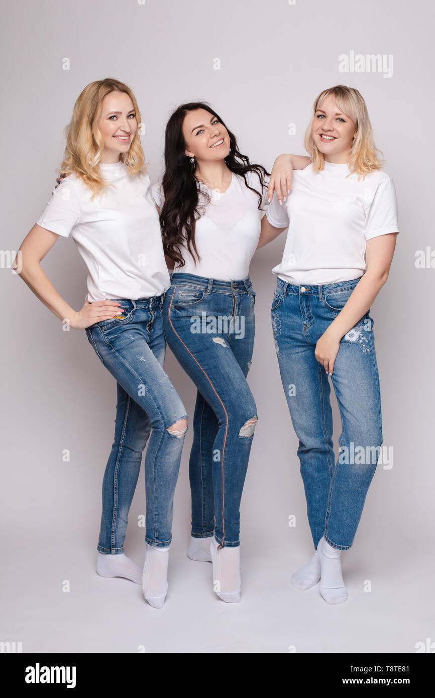Tres hermosas mujeres de camiseta blanca y jeans posando Imagen De Stock